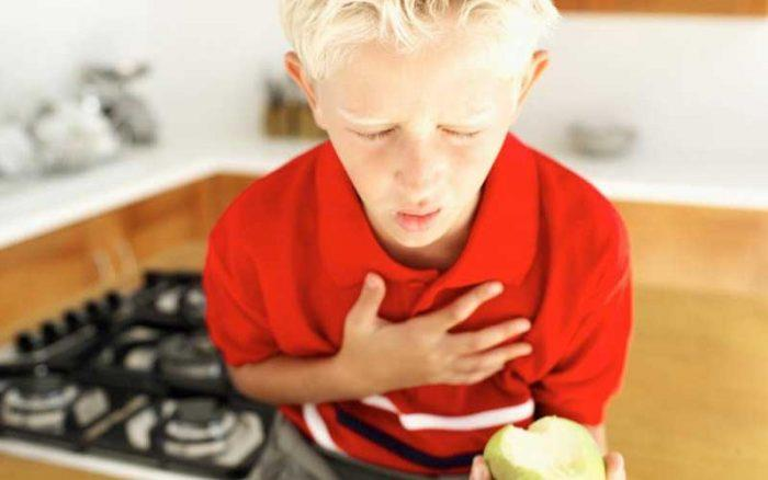 Blonde boy child clutching chest in pain holding a pear