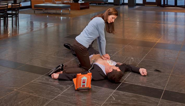 Person performing CPR with a St John defib