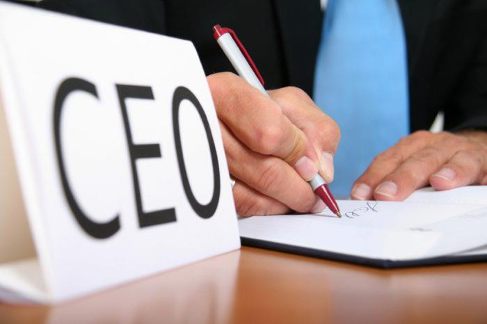 Person writing on a piece of paper with CEO card on desk
