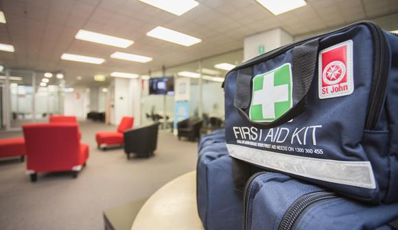 3 first aid kits stacked on a table in a room