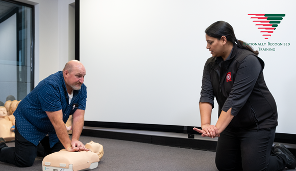 First aid trainer showing a man how to do CPR compressions