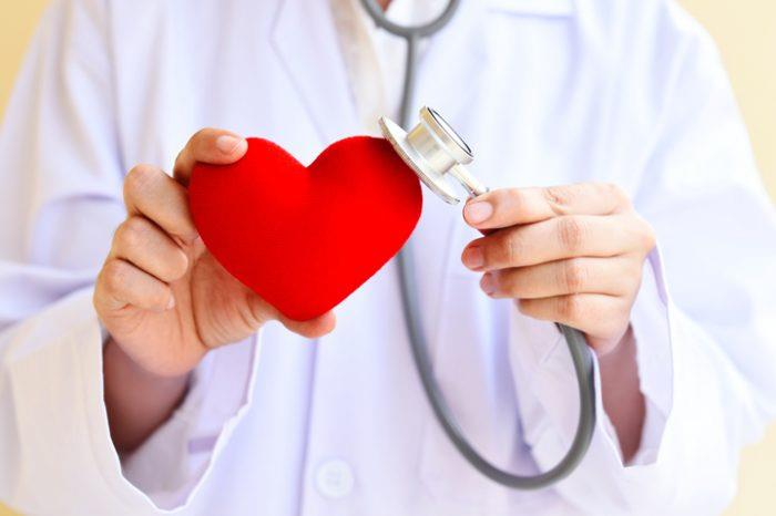 Doctor holding stethoscope to toy heart