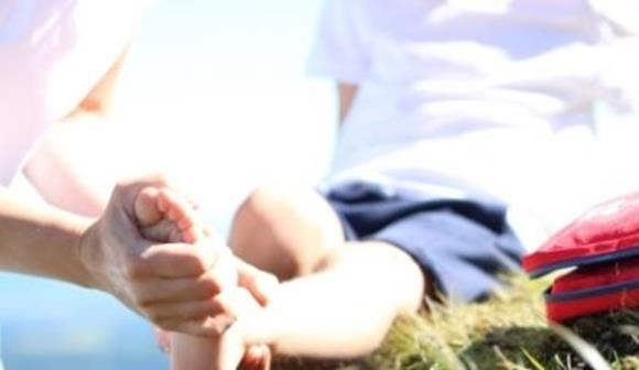 Applying first aid to child foot in park