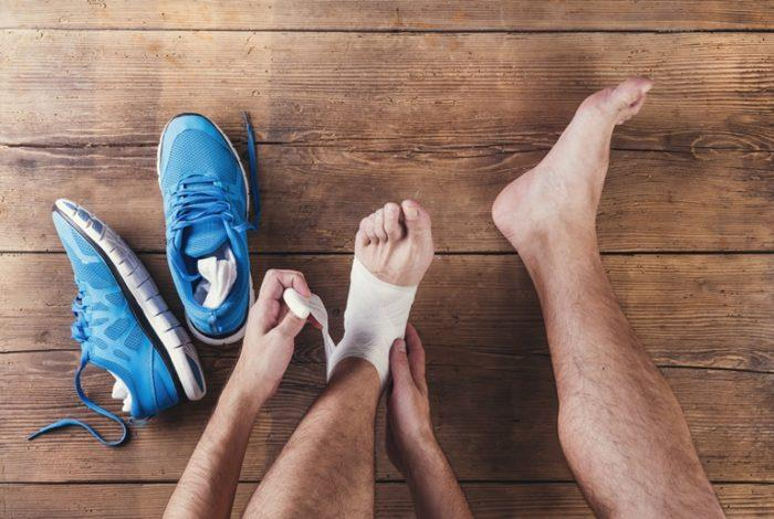 Injured Runner applying bandage to foot