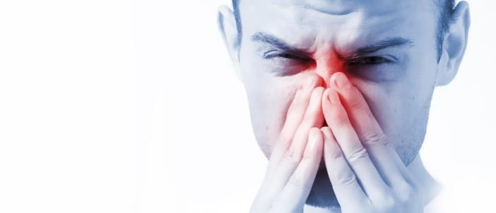 Man holding his nose in pain