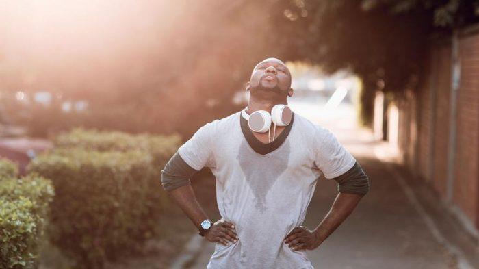 Runner with headphones sweating through shirt from running