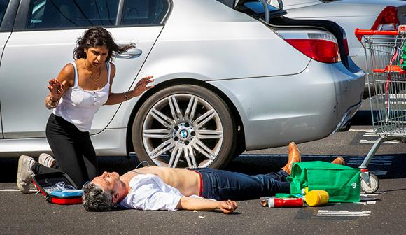 woman using a defibrillator on a man in a car park