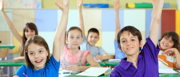 Elementary School Kids with their hands up