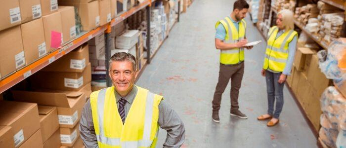 man in fluro safety vest standing in a warehouse workplace with colleagues