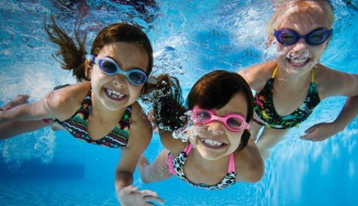 children swimming underwater smiling at the camera