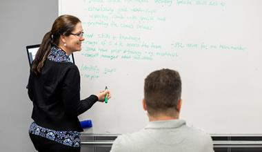 woman writing on class whiteboard