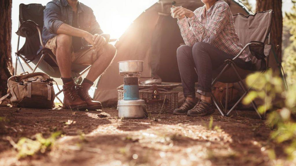 2 people camping in the wilderness enjoying a drink