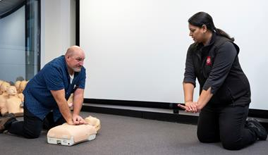 St John first aid training trainer with student on CPR manikin
