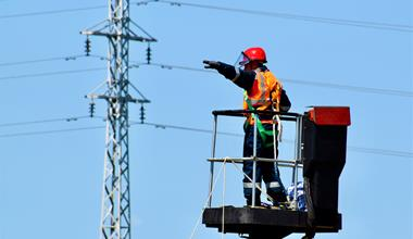 Electrical worker on a crane directing movement