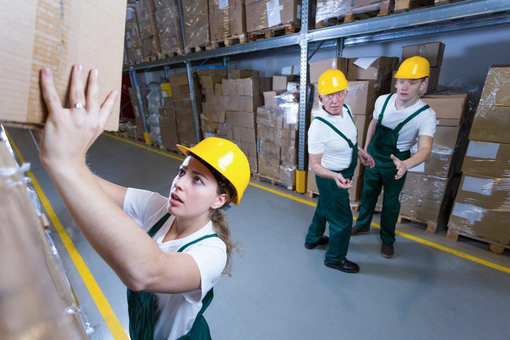 woman worker struggling to put heavy box away up high with coworkers worried watching in the background